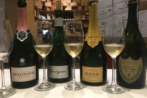 Lineup of champagne in bottles and glasses